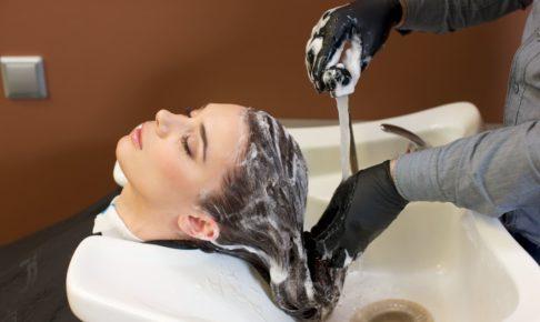 手袋をつけてシャンプーする美容師